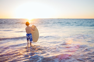 Child using a skim board at the beach at sunset