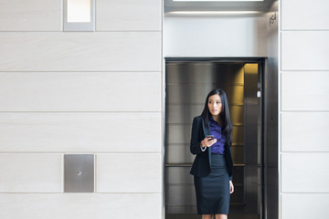An Asian woman walking out of an elevator holding a smart phone