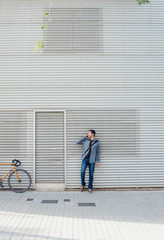 Young man in front of a metal building talking on phone
