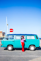 young woman in red posing with retro minivan