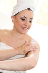 Portrait of smiling young woman applying moisturizing cream