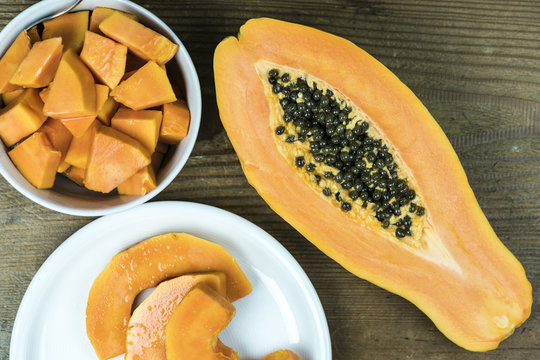 High angle view of papaya cut in half with small pieces in bowl against wooden background
