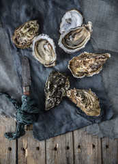 Oysters with a vintage cloth on a rustic wood surface