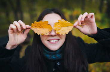 Young lovely woman covered her eyes with yellow autumn leaves and cheerfully smiles. walking in the autumn park and fun with yellow autumn leaves.