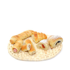 variety assortment of various  baked filled pastry on wicker rattan coaster isolated over white background