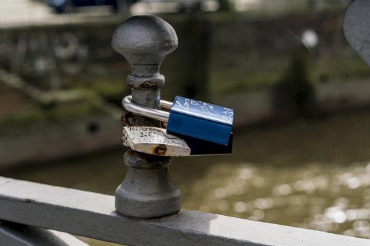 Two padlocks fixed at bridge railing as symbol of love