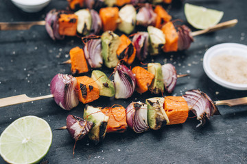 Food: Barbecue skewers with onions, sweet potato and avocado with chili strings and lime, caribbean veggie style