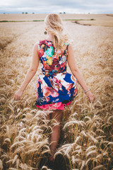 Girl in a floral dress walking through a wheat field in the Spring time