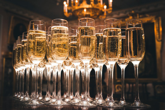 A lot of glasses of champagne in a luxurious atmosphere. Stylish, toned photo. Secular reception, new year, wedding