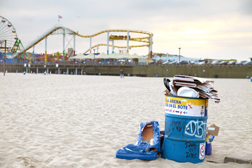overflowing rubbish bin on beach with Santa Monica pier in background