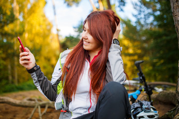 Picture of happy woman with cellular phone in autumn forest