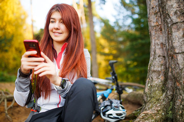 Photo of happy woman with smartphone in autumn forest