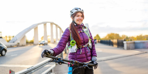 Image of sports woman in helmet on bicycle on bridge in city