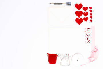 Display of love letter items on white background. Assortment of cards, envelopes, hearts, ribbon and ink pen.