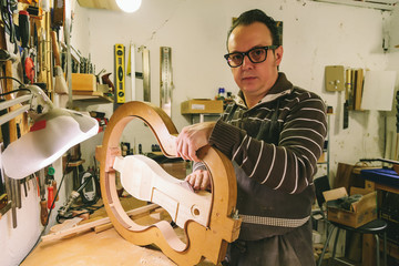 Man working at a Workshop with Musical instruments