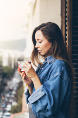 A beautiful and young Caucasian girl in big jeans shirt is holding a large cup of coffee while standing in a comfortable glazed balcony on sunny a autumn day