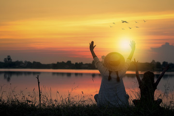 happy and funny concept, silhouette of two young girls sitting and showing hand besides bank of river