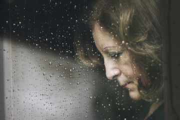 Mature woman standing at the window watching the rain