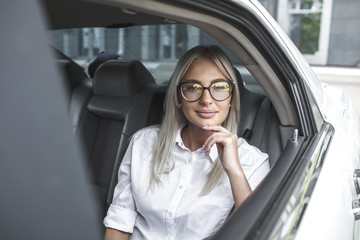 Portait of confident businesswoman with glasses in car