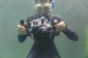 Man diving with underwater DSLR camera case