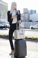 Young businesswoman in the city with cell phone and luggage