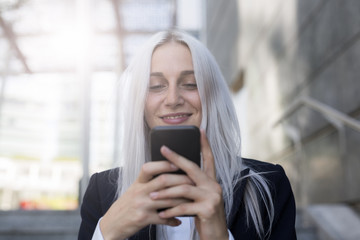 Smiling young businesswoman checking cell phone in the city