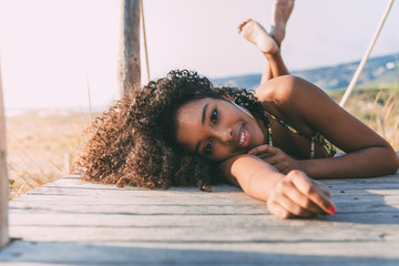 Beautiful young black woman lying down in a  wooden foot bridge at the beach .