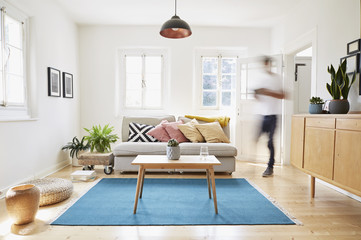 Germany, North-Rhine-Westphalia, Cologne, man walking in bright modern living room in an old country house