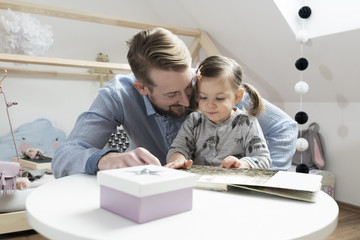 Father and daughter looking at photo album in her nursery