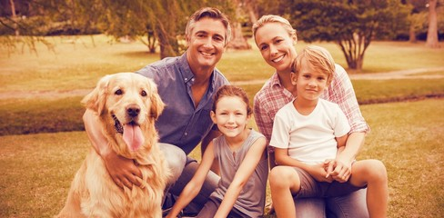 Portrait of family enjoying with dog at park