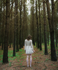 Girl in pine forest in white dress