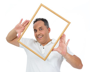 Funny man holds frame frame around face. He is overweight and is wearing a white polo..