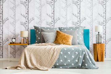 Bed against forest motif wallpaper