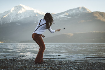Young woman throwing stones in the water