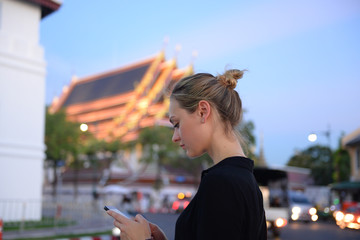 Tourist is using smartphone and chatting when visiting in Bangkok, Thailand.