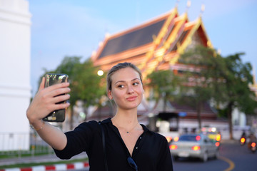 Beautiful woman is selfie in front of the temple while travel in Bangkok, Thailand