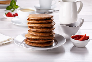 Stack of chocolate pancakes with strawberries.