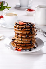 Stack of chocolate pancakes with chocolate topping and strawberries.