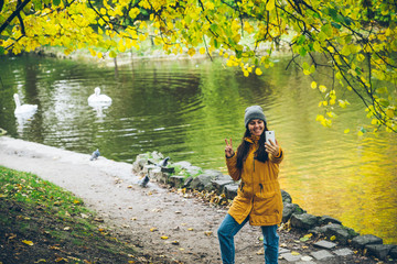 woman taking picture in city park on the lake