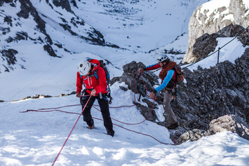 two mountain climber rappeling  and fixing ropes on a  mountain