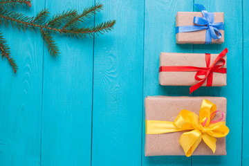 Turquoise background for Christmas cards. Background for Christmas wishes. Blue wooden boards. Christmas card. Christmas gift. Holiday gifts are stacked. Sprig of fir on a wooden Board.