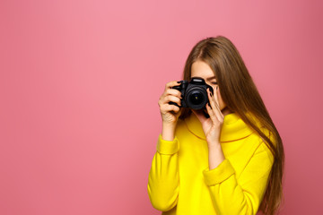 Girl photographer! Beautiful young girl takes a picture. In a yellow sweater on a pink background. Copy space