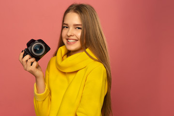 Girl photographer! Beautiful young girl smiles, holds the camera in hand. In a yellow sweater on a pink background. Copy space