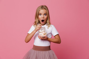 Portrait of an excited little girl holding jar of marshmallow