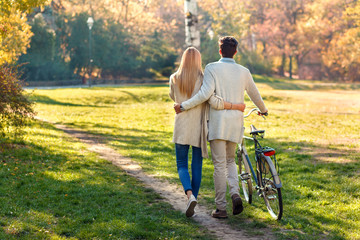 Back view of young couple with bicycle walking in park on sunny autumn day.