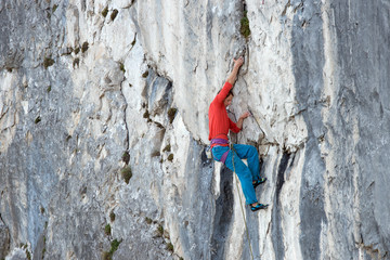 A mountain climber is hanging on the wall of the one of the Barmsteine rock towers, which are part of the Hassel Mountains in the Bavarian Alps between Austria and Germany.