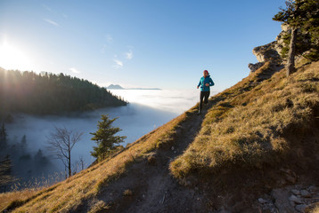 A young woman does mountain running or a trail run at the beautiful Nockstein mountain in Salzburg, Austria.