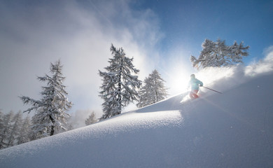 A snow covered skier races down in an off-piste area in the Zauchensee ski region, Austria. Fotobehang