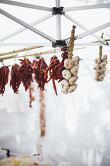 Dried garlic and red peppers hung at farmers market stand in Italy