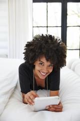 African American woman working on tablet in bedroom